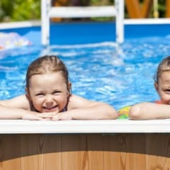 Two young girls peeking over the side of an above ground swimming pool, with a wooden perimeter fence in the background